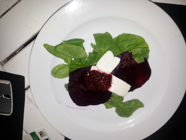 Goat cheese served on a bed of beetroot and rucola, then drizzled with raspberry and balsamic reduction